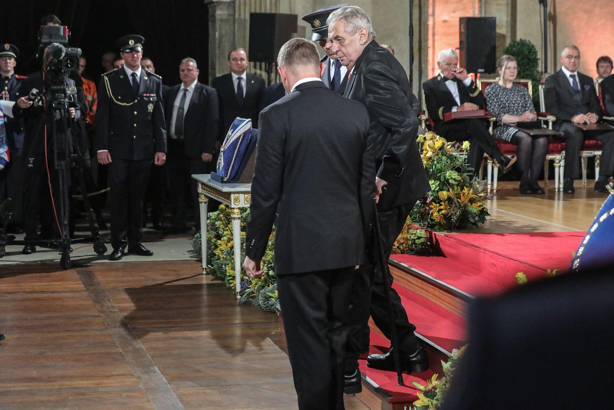 Po všech oceněných sešel prezident tři schody a usadil se vedle své manželky. Už na začátku ceremoniálu vysvětlil, že ho velmi bolí nohy, ale že za rok to určitě bude lepší.