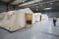 V několika halách vojáci staví armádní stany.