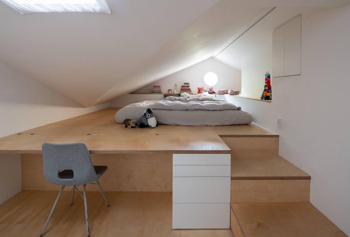 Spaní pro dítě je na podestě, která pozvolna přechází v pracovní stůl.