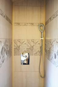 ... i sprchu. Na vodu má rodina vlastní zásobníky a ve dřevě nad sprchou je skrytý bojler.