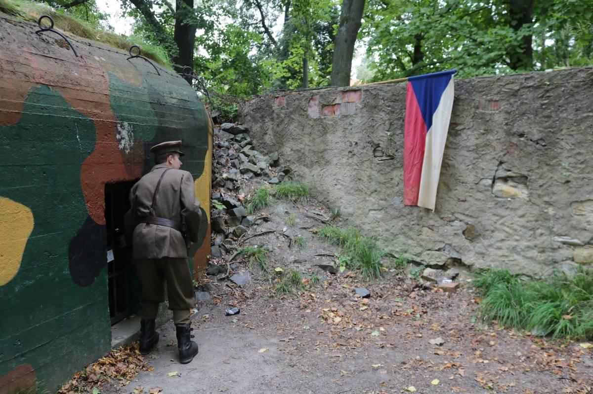 Vlajka je dobová z roku 1938, bunkrem provádějí dobrovolníci ze skanzenu.