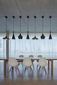 Soukromou část propojují s venkem celoplošná okna, z kterých je výhled na celé středohoří. Nad jídelním stolem jsou atypická závěsná svítidla.