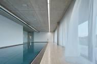 Uvnitř luxusní vily, která má okolo 1000 metrů čtverečních užitné plochy, je bazén se stropem z pohledového betonu.