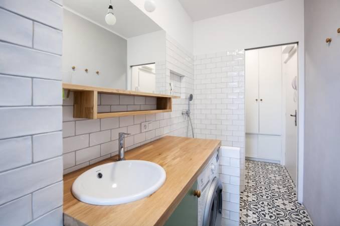 Do limitované koupelny nechaly architektky vyrobit koupelnovou skříňku s deskou, již opřely o přepážku oddělující sprchu od umyvadla. Díky tomu se sem dnes vejde i pračka.